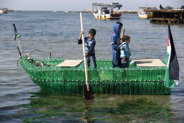7f03f74eed1 Palestinian children pose for a picture on a makeshift boat made of plastic  bottles on April 18