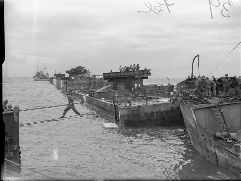 """Mulberry Harbour, Arromanches: """"Phoenixes"""" laid in line off the coast at Arromanches, while a soldier makes a hazardous wire rope crossing. These formed part of the Mulberry harbour."""