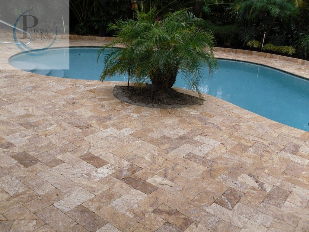 here, travertine marble pavers provide a stylish elegance to this