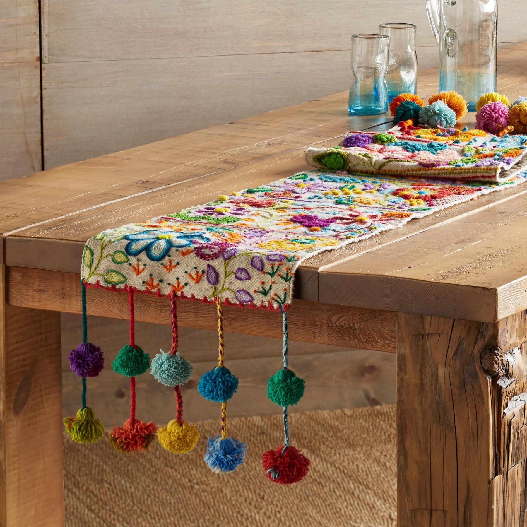 POMPOSA TABLE RUNNER -- Each of these colorful runners is one of a kind, made by the women in the villages around Cusco, Peru, as stitch samplers to show off their embroidery skills. Handloomed wool, with bright pom-poms on each end. By Jenny Krauss. Catalog exclusive. Approx. 12W x 62L. #embroidery
