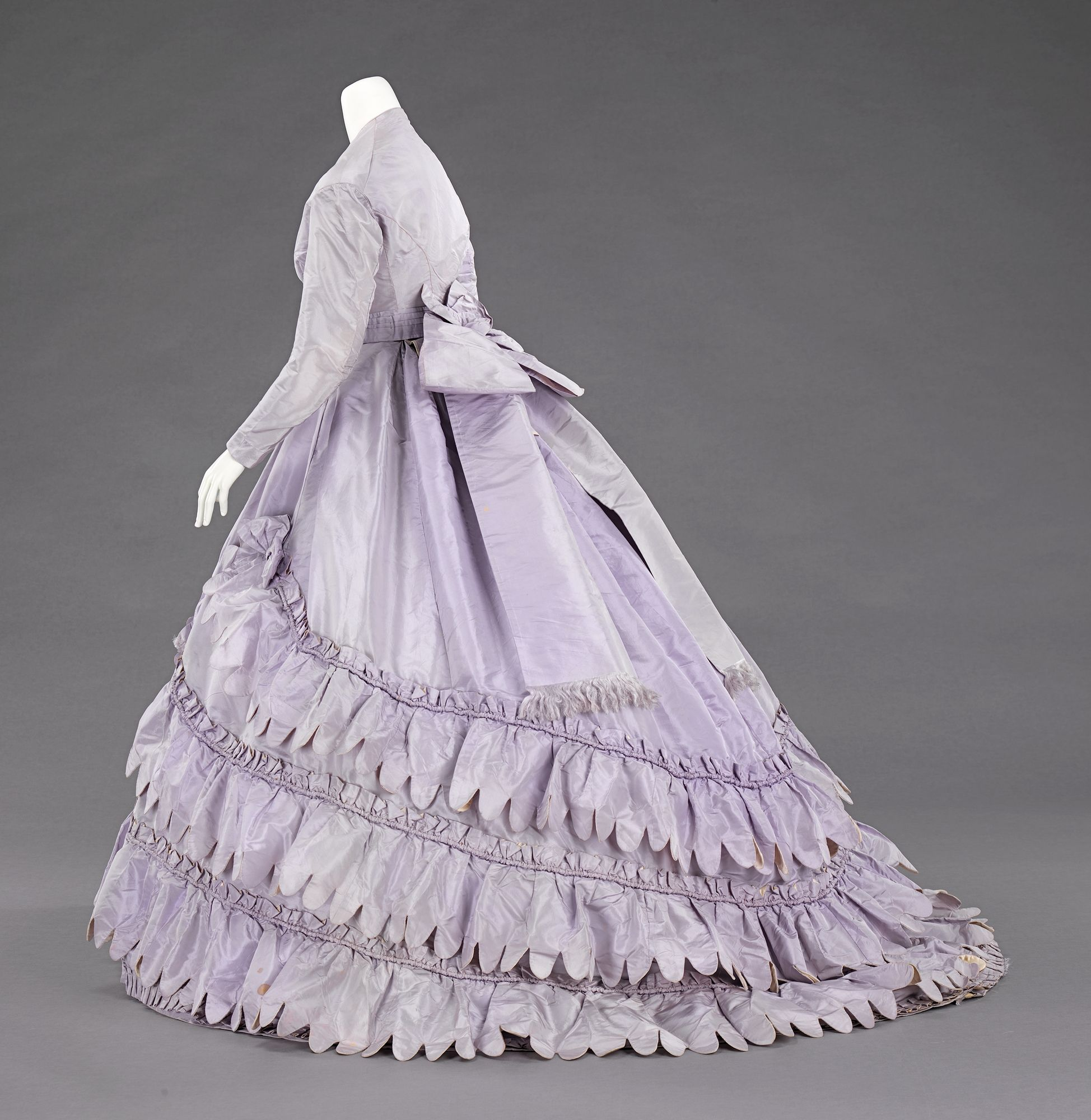 The female silhouette of the middle of the 19th century consisted of a fitted corseted bodice and wide full skirts.  The conical skirts developed between the 1830s, when the high waist of the Empire silhouette was lowered and the skirts became more bell shaped, to the late 1860s, when the fullness of the skirts were pulled to the back and the bustle developed