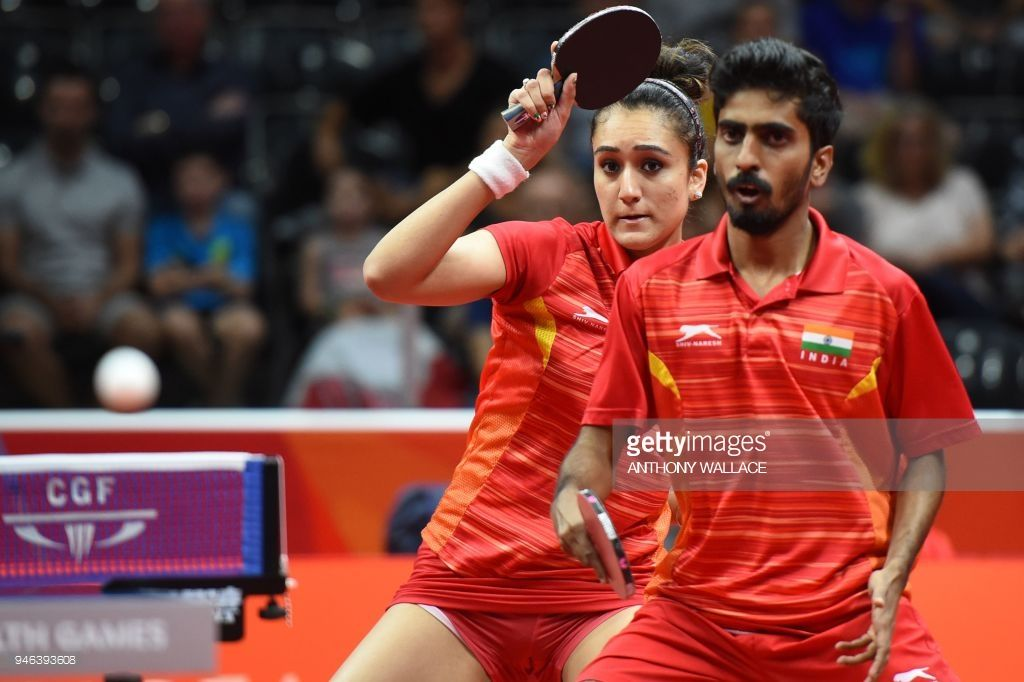 India S Manika Batra L Plays A Shot Past Teammate Sathiyan Gnanasekaran Against India S Sharath Achanta And Moum Tennis Match Commonwealth Games Table Tennis