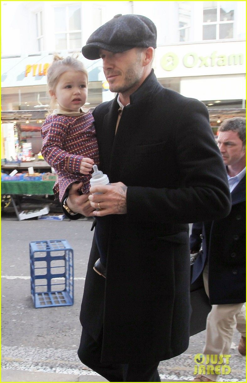 c6417872c39 David Beckham looks dapper in his newsboy cap while holding his daughter