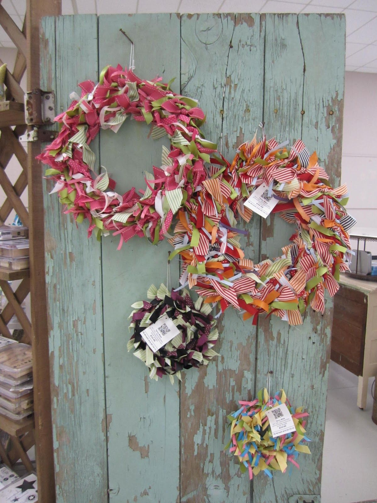 We actually used an old door to display these ribbon wreaths. It's attached to the lattice shelf next to it.