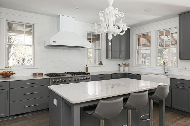 Murano chandelier over a charcoal gray island fitted with ...