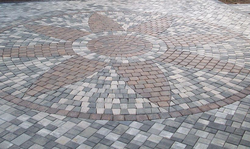 Multi Colored Pavers In A Random Pattern Accented With Flower