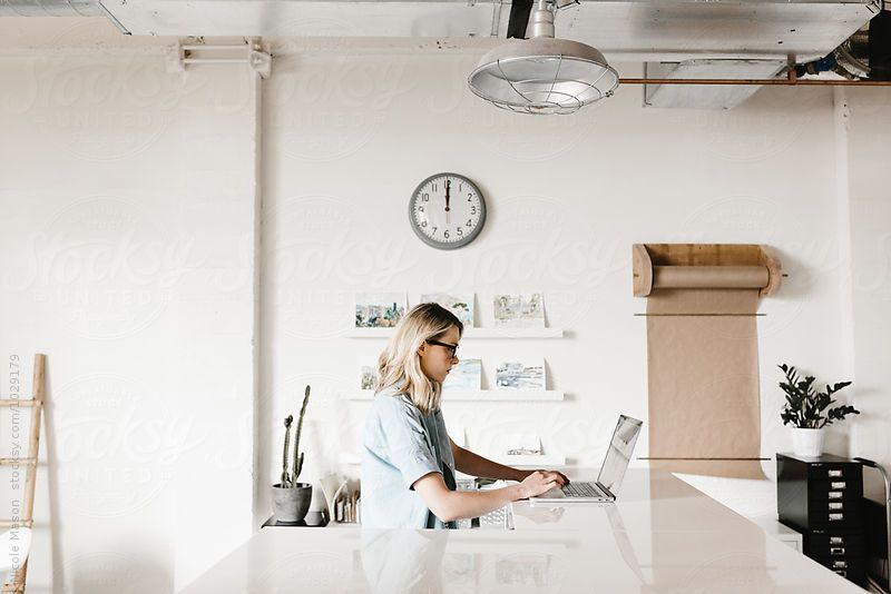 woman working on laptop in creative minimal office  by Nicole Mason for Stocksy United