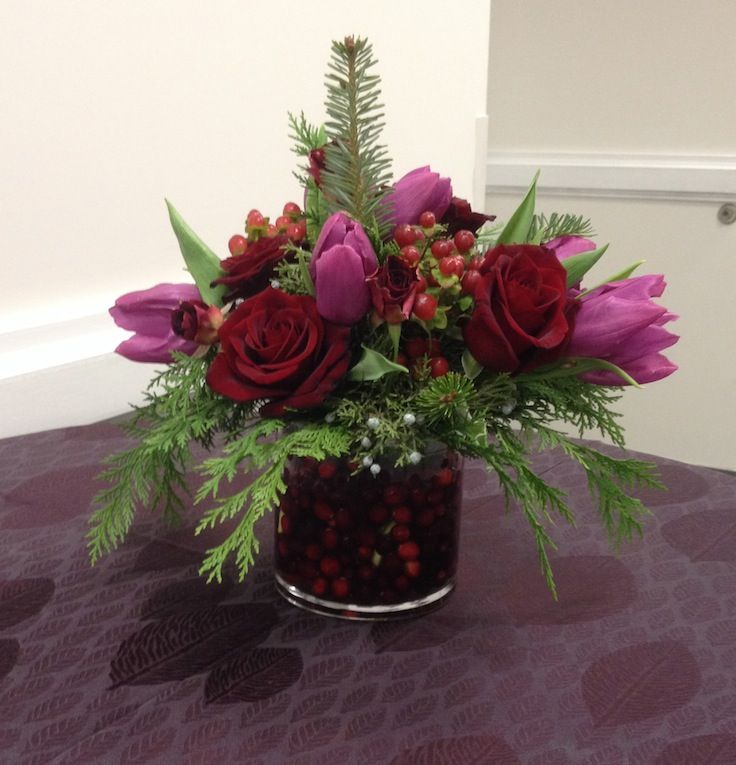TableArt- Holiday- Fresh cranberries in a glass vase with an arrangement of winter greens, purple tulips, red roses and hypericum berries {www.TableArt.Net}