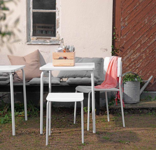 Patio con un taburete, una silla y una mesa de exterior en blanco ...
