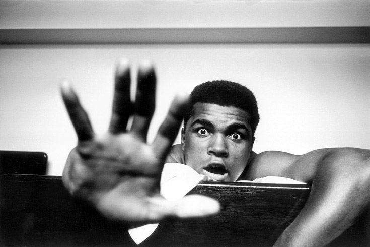 Muhammad Ali, ehemals Cassius Clay, US-amerikanischer Boxer. Aufnahme aus dem Jahr 1963. Ali liegt auf seinem Hotelbett in London. Mit seinen Fingern zeigt Ali dem Fotografen, über wie viele Runden der bevorstehende Kampf gegen Henry Cooper seiner Ansicht nach gehen werde, bis er den Briten k.o. geschlagen haben werde. Fotografie: Len Trievnor