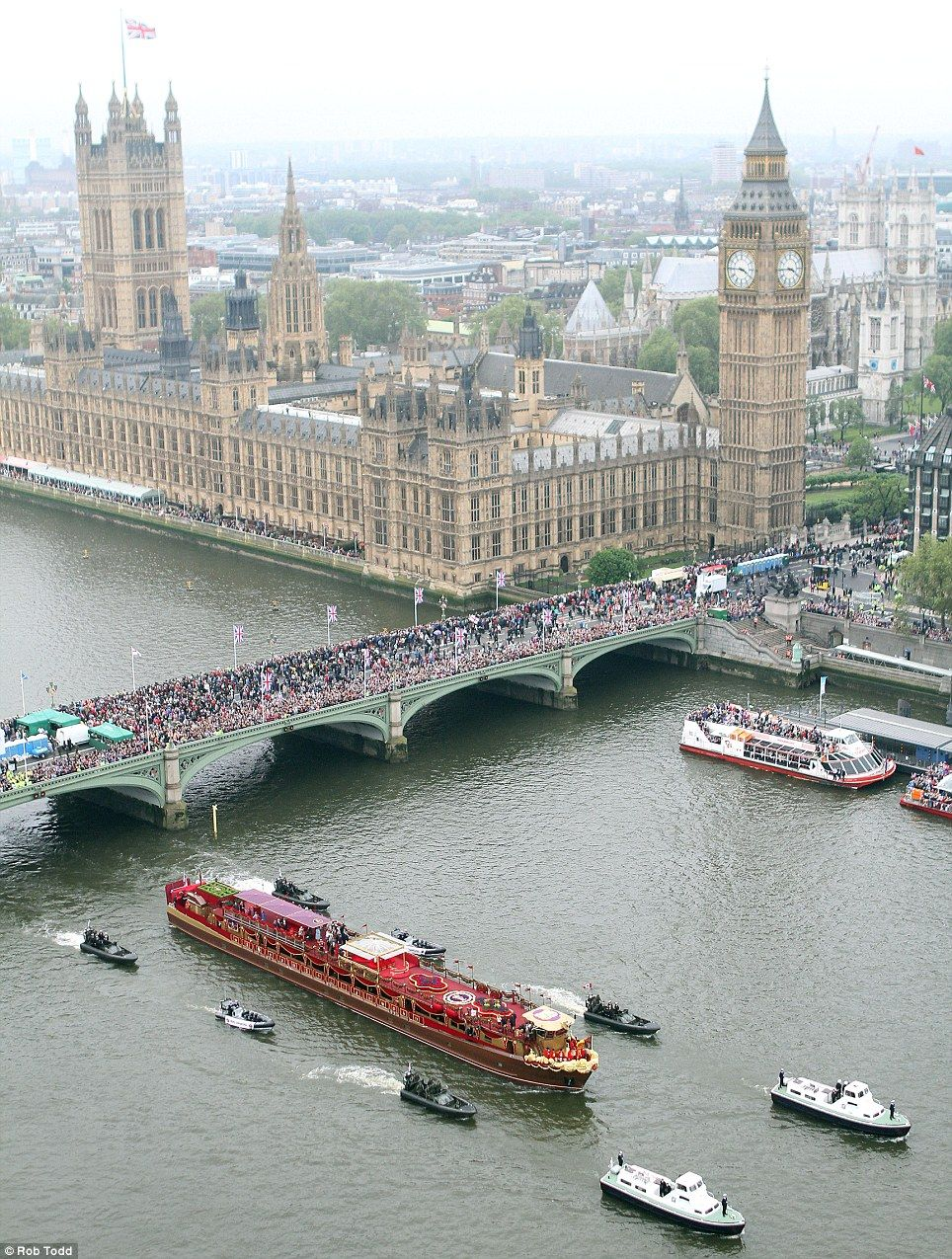 The view from the London Eye: Crowds pack Westminster Bridge as the royal barge and escort passes the Houses of Parliament. Jubilee river pageant - June 2012.