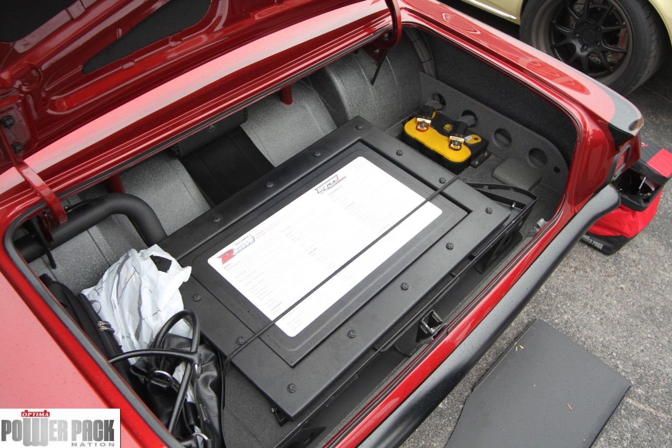An OPTIMA YELLOWTOP tucked in the trunk of the Runt Nova