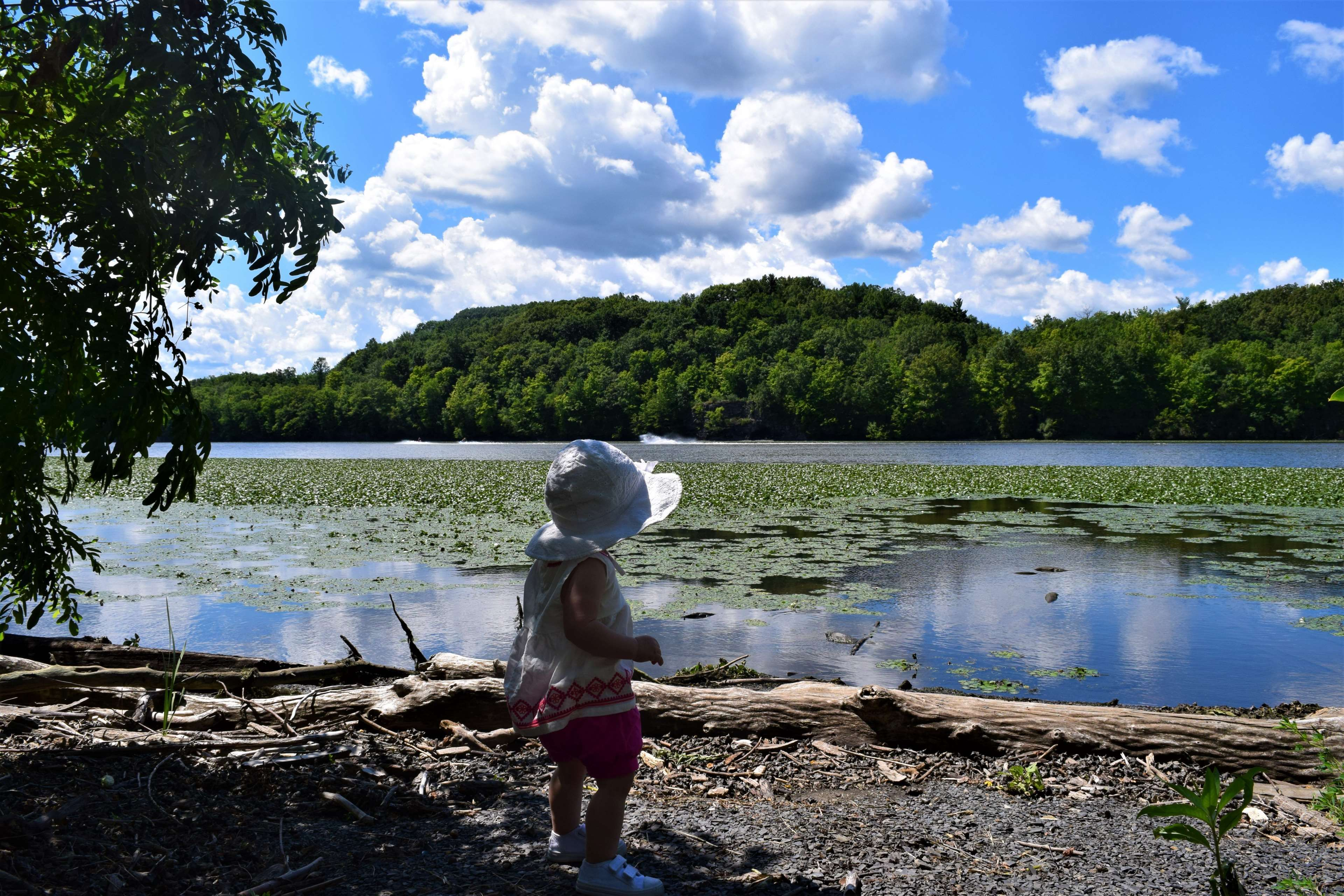 baby beach child clothes hat kid landscape outfit river sky
