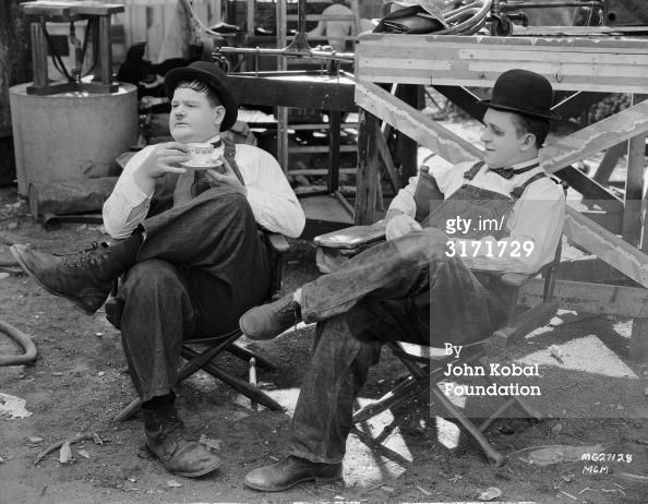 Stan Laurel with a blackened eye and Oliver Hardy, who is sipping tea while on break from filming