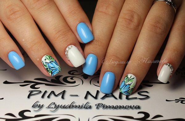 O floral embelezou pregos.  Obtenha suas unhas embelezadas com o padrão floral azul e acento de cor branca, juntamente com os diamantes.