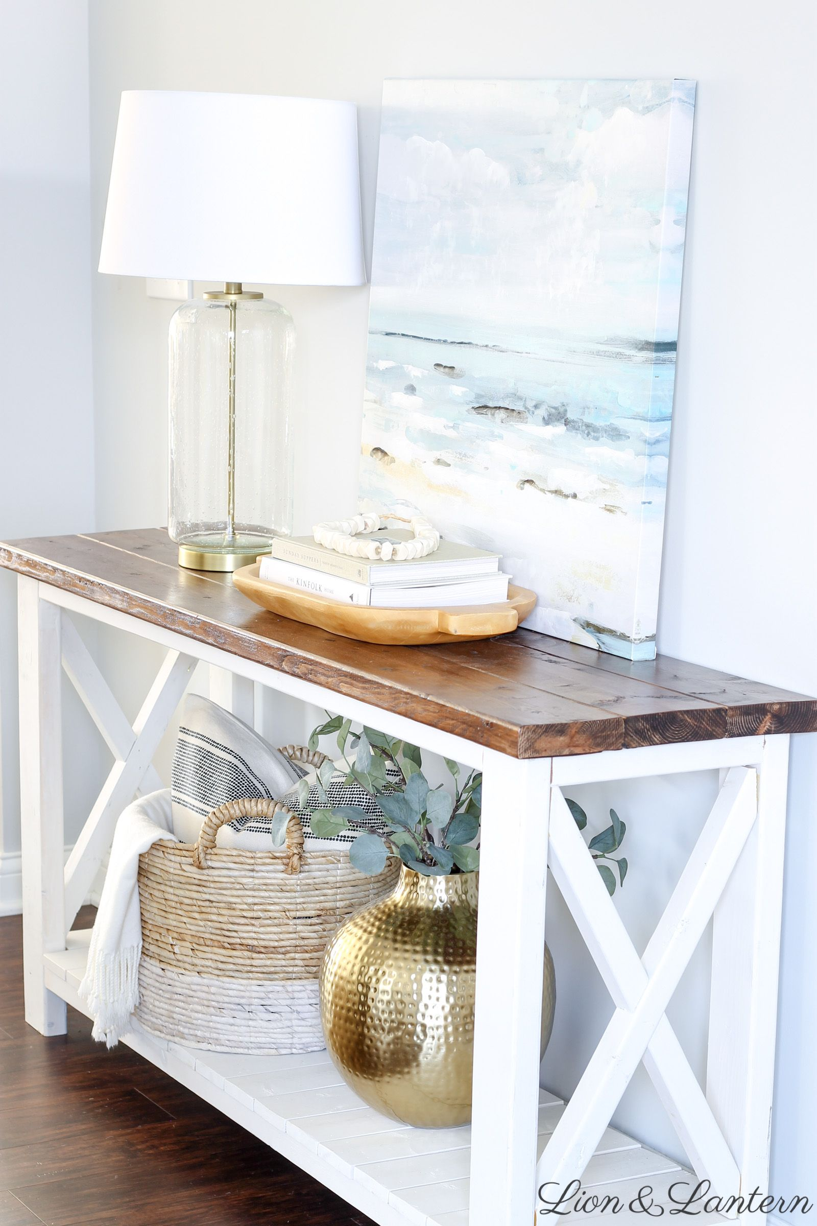 Easy Coastal Entryway Styling at LionAndLantern.com | coastal farmhouse, coastal decor, modern, minimalist, bone beads, ocean painting, Ana White rustic x console #coastallivingrooms