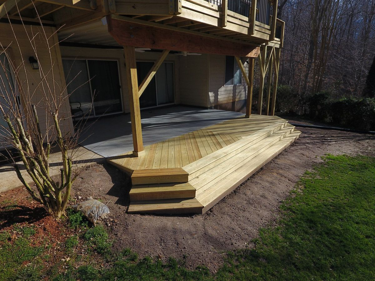 Under Deck Patio With Pressure Treated Pine Landing And Stairs Is Protected From Rain With Timbertech Dryspac Concrete Patio Cost Patio Pictures Concrete Patio