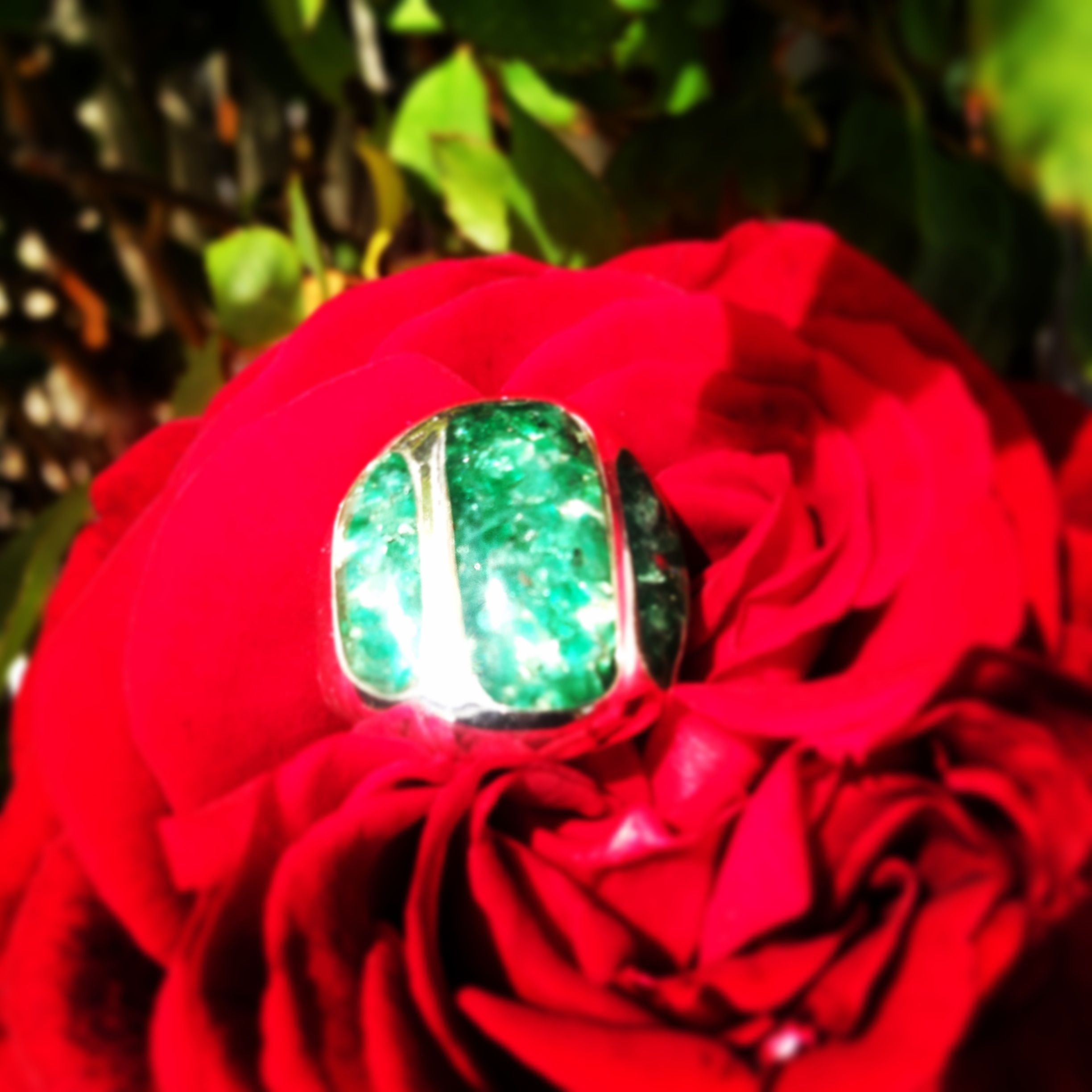 Indulge in sheer sublimity with this luxurious Emerald ring. 5.5 carat of genuine Emerald gemstone fragments inlaid in resin and cradled in a 19mm x 30mm 925 sterling silver ring harmoniously matching its unique design.