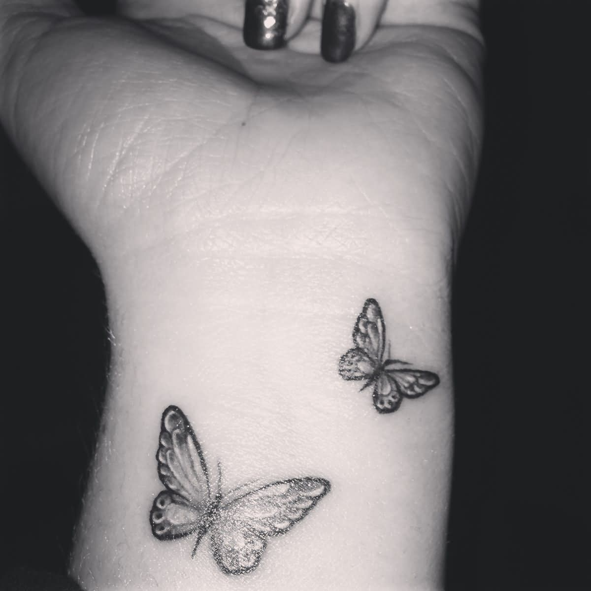 Grey And Black Butterfly Tattoos On Wrist For Girls Butterfly Wrist Tattoo Butterfly Tattoo Butterfly Tattoo Designs