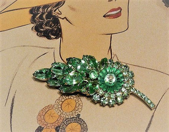 ITEM # 121657  Beautiful verified DeLizza & Elster aka Juliana leaf shape rhinestone brooch.   Top row of the brooch consists of a large green vaseline glass margarita rhinestone with a small pink aurora borealis on the tip, 11 small vaseline accent glass rhinestones surround the margarita, 3 large vaseline glass navettes, a round vaseline glass foiled rhinestone and 4 medium green glass navettes. Bottom row consists of 6 large vaseline glass navettes, 13 medium vaseline glass round accen...