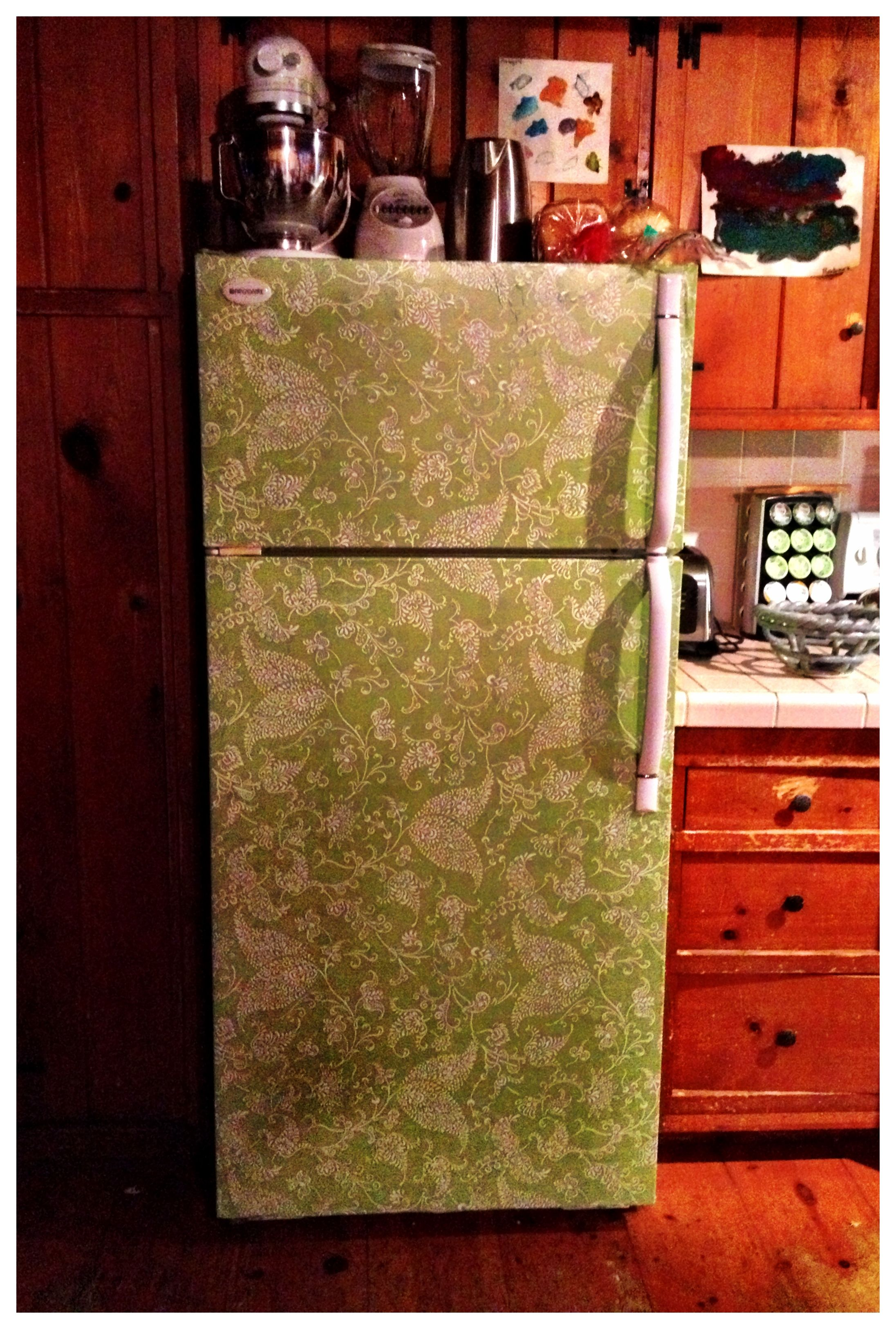 Diy cover a scratched dented fridge with contact paper to give your kitchen new life
