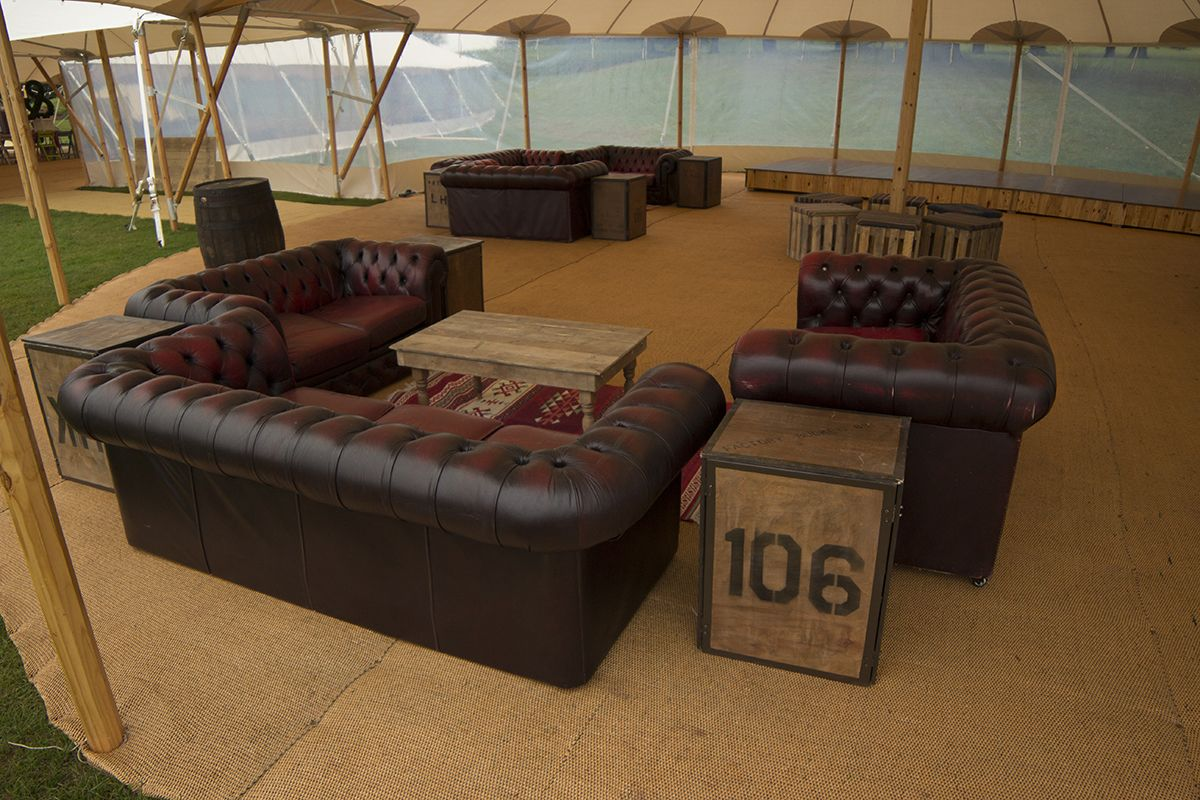 Oxblood Chesterfield sofas in a vintage marquee. Wedding