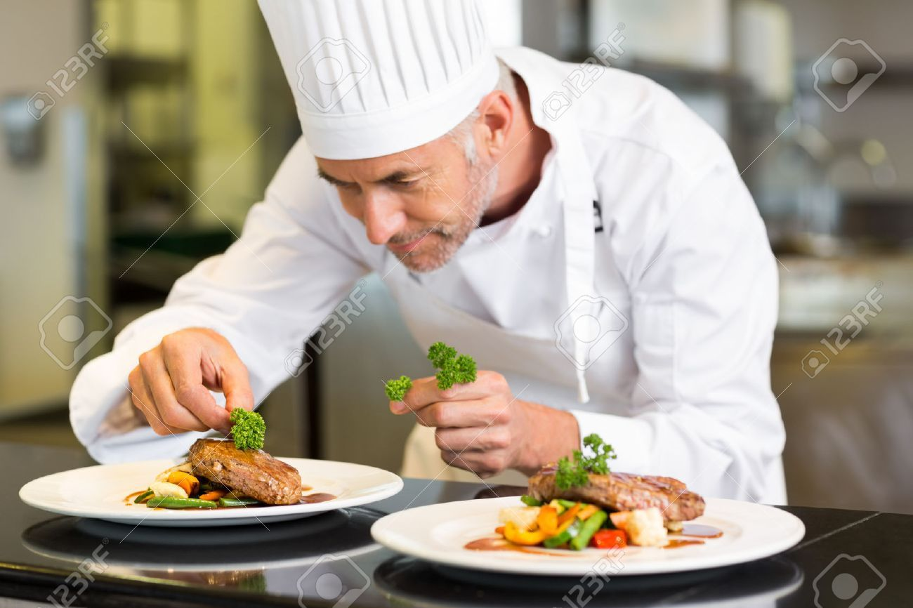 Closeup of a concentrated male chef garnishing food in the kitchen , #Ad, #male, #concentrated, #Closeup, #chef, #kitchen