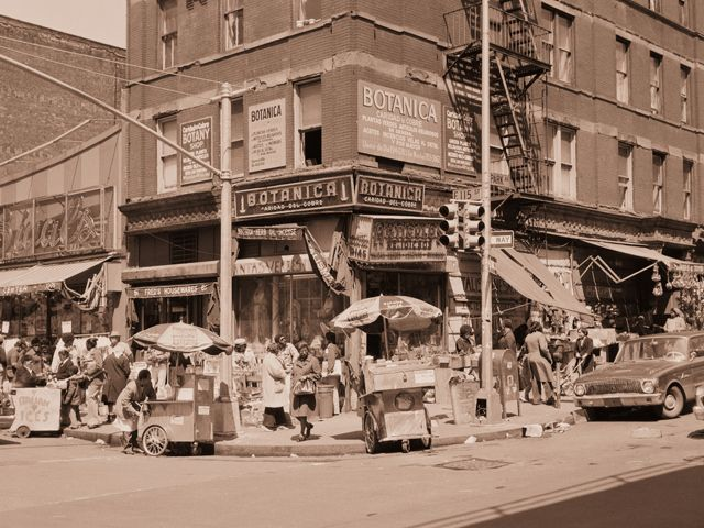 Street scene of people at small shops in Spanish Harlem El