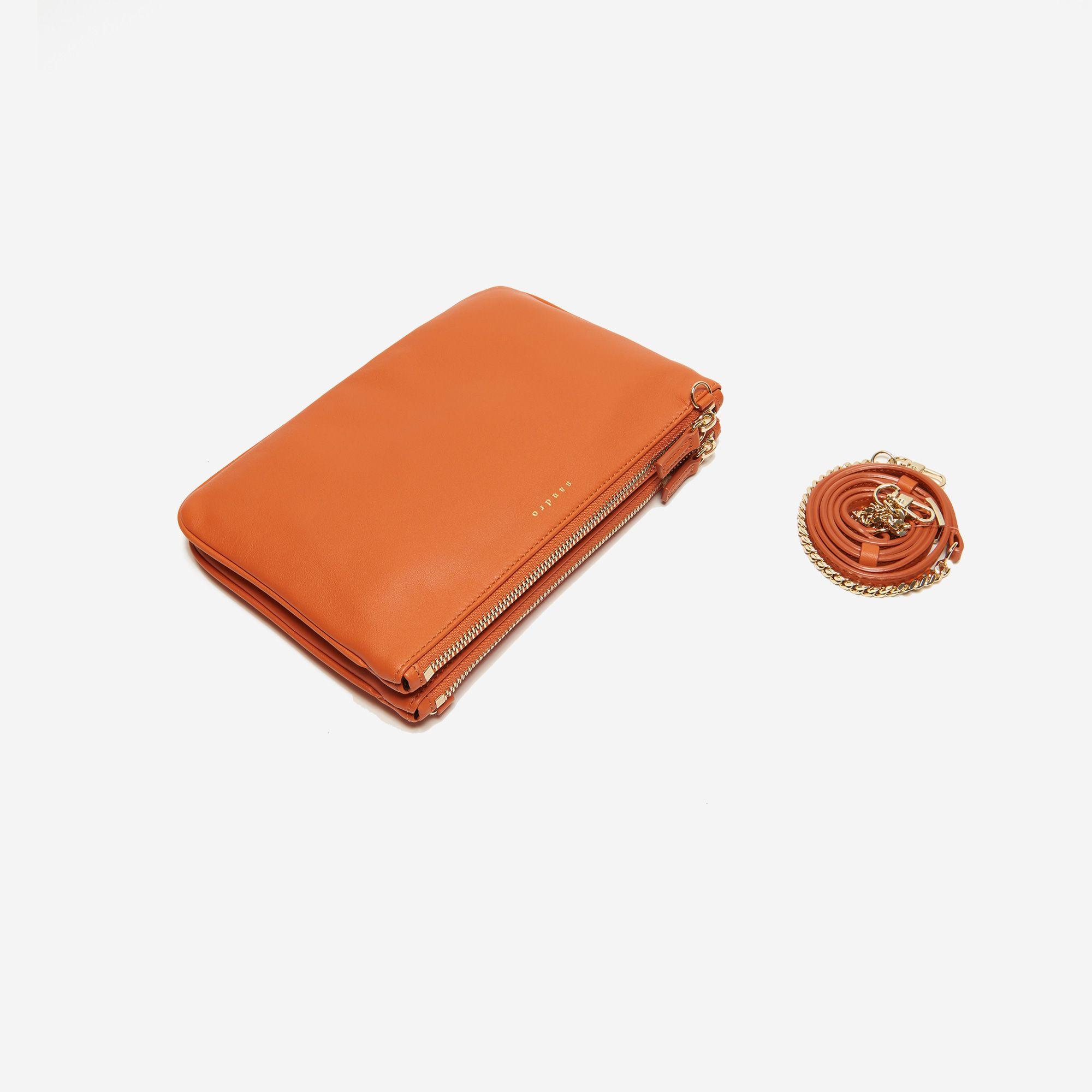 Sac Sandro à double pochette en cuir lisse. Fermetures zipées de couleur contrastée. Anse amovible en chaîne et en cuir. Dimensions: 23 x 16 cm.
