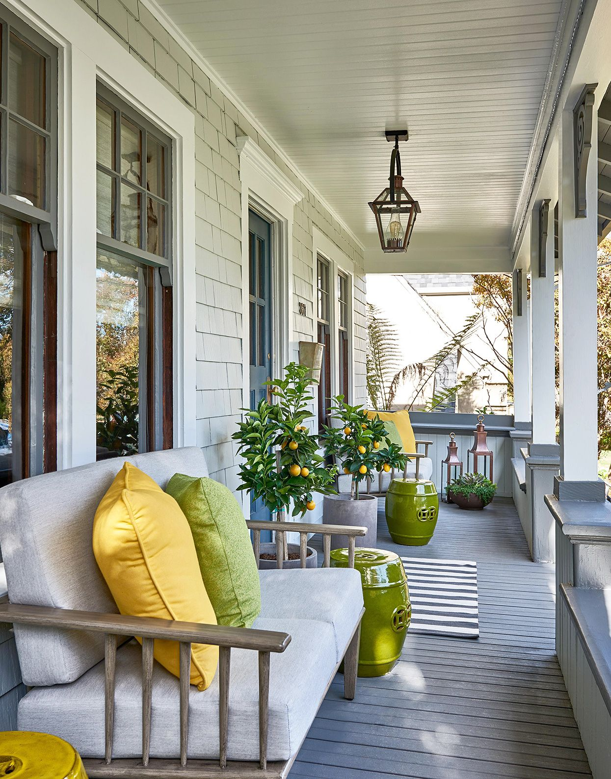 Porch ideas don't have to be complicated. Sometimes a simple swap of the color palette can make your design feel fresh again. #fourseasonsroom #frontporch #porchideas #patiodecor #homedecorideas #bhg