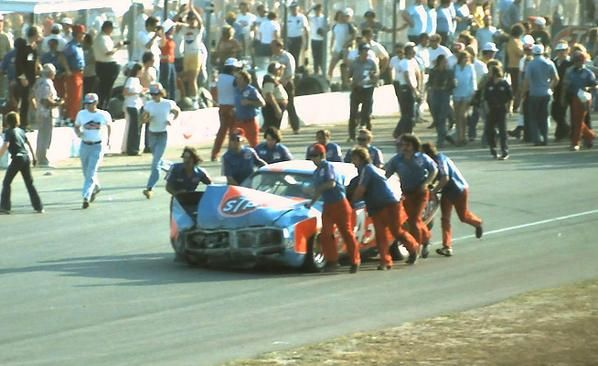 Richard Petty has accident and the crew helps take him behind the wall to repair the 43 car.