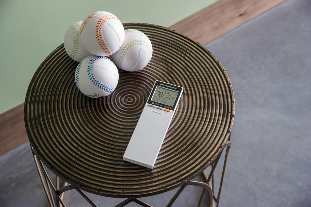 A side table hosts the remote for the game room air