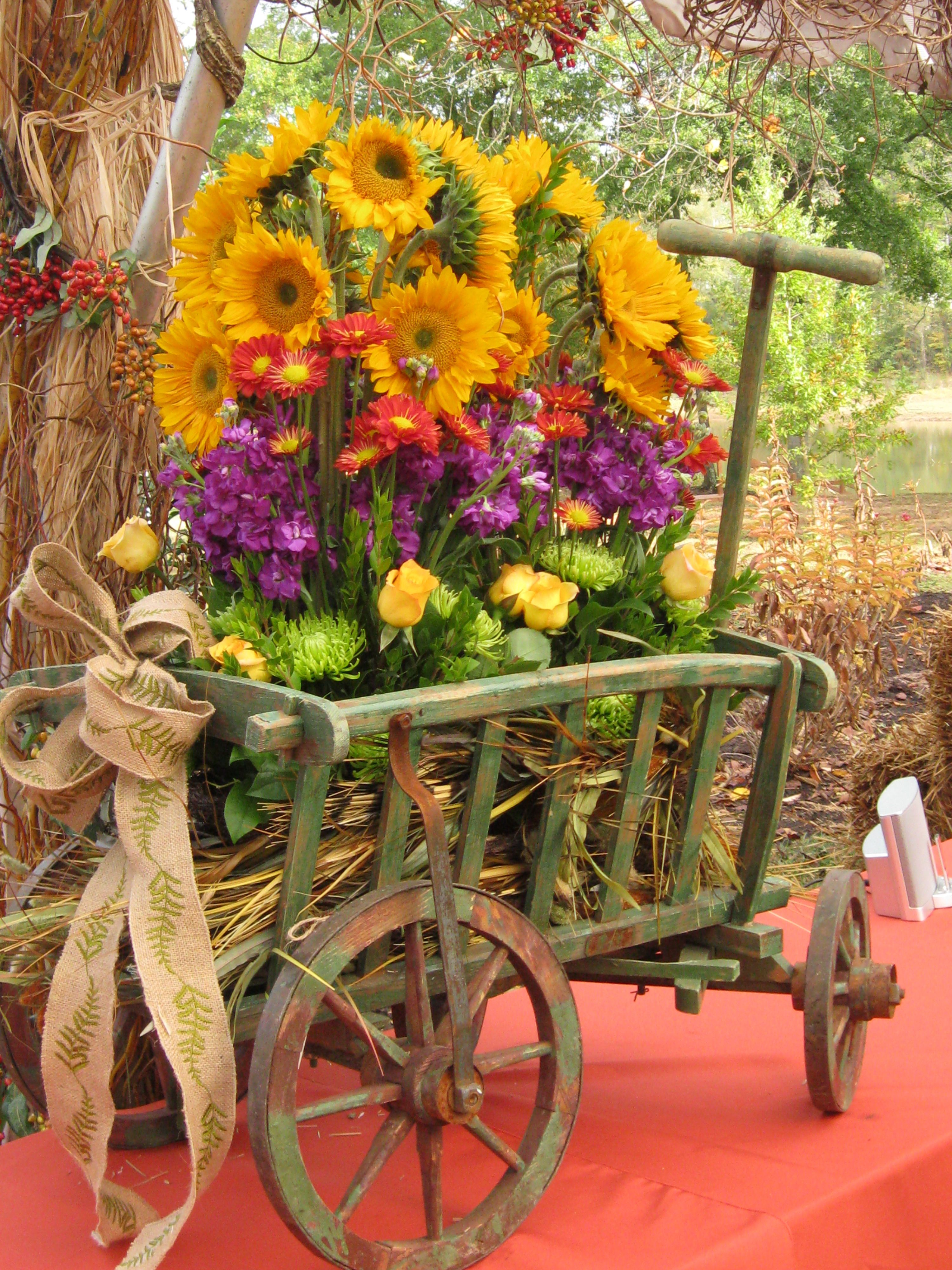 Sunflowers and bright colored blooms fill this wagon