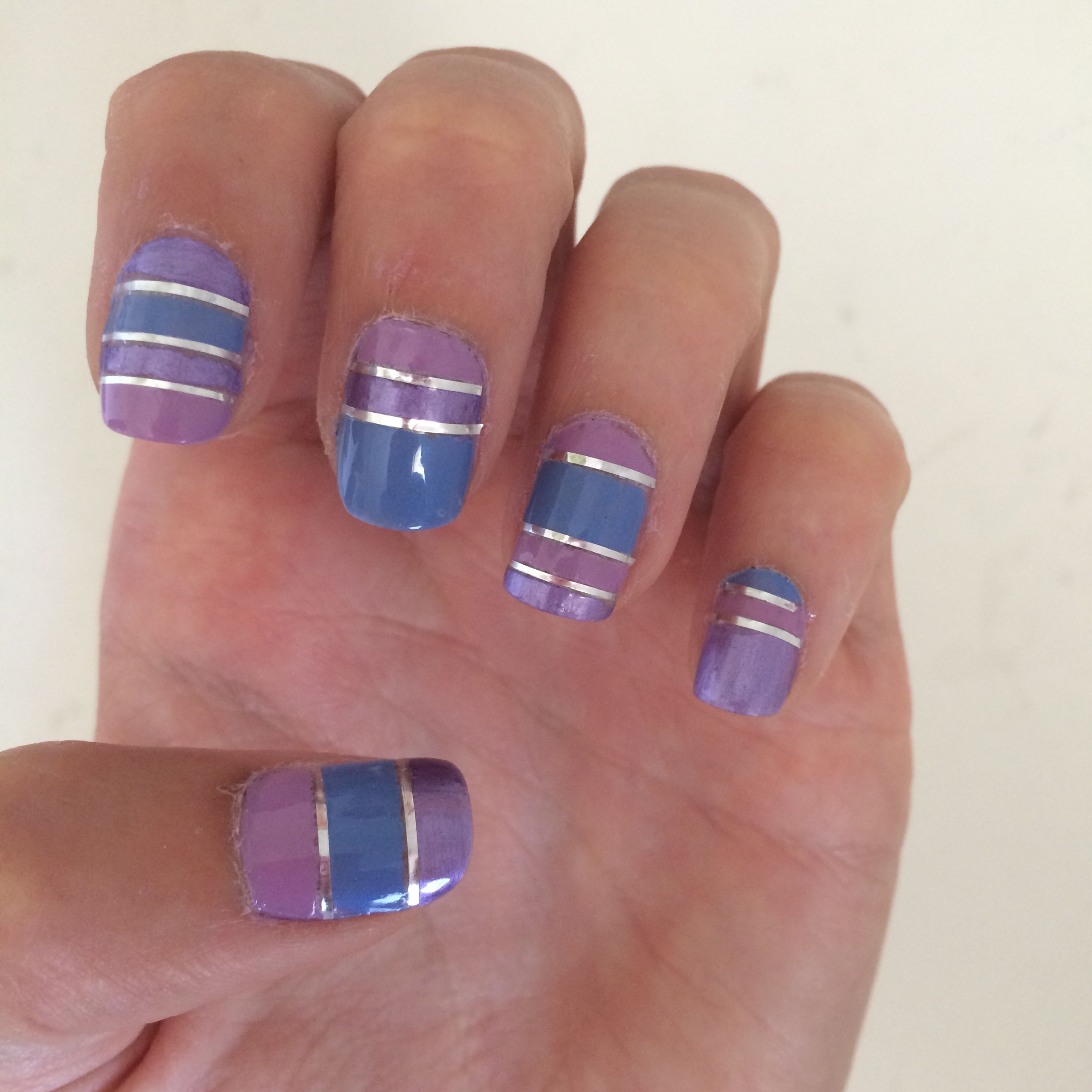 Stripes nails in blue, lilac and pink with silver lines.