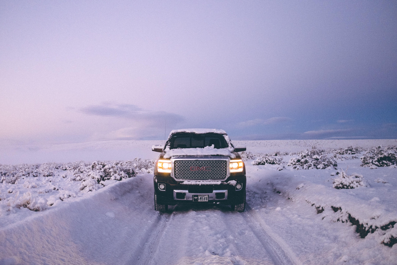 Black GMC Sierra Denali on snow covered road  Cars