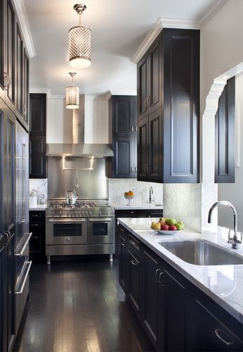 Dark Cabinets With A Brown Floor And Marble Counter Tops Back