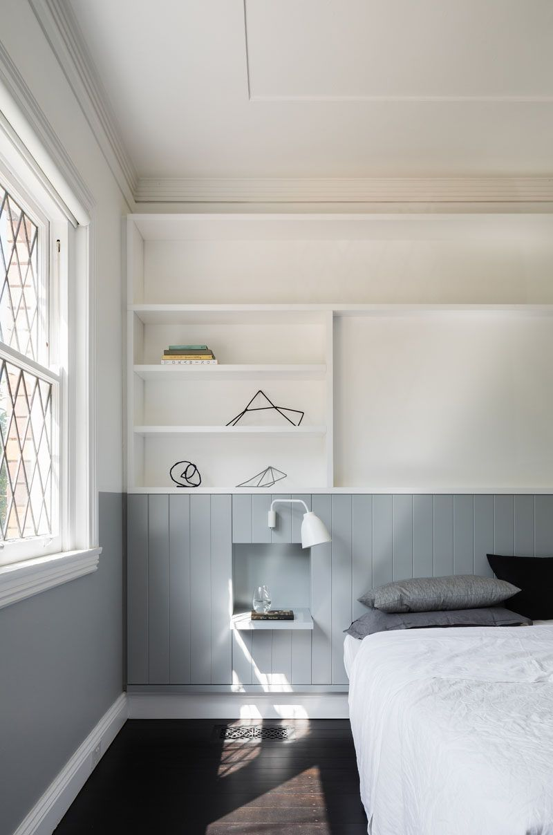 In this modern bedroom, a grey strip wraps around room and turns into the headboard behind the bed. A white shelving system above the bed provides extra storage and display room for decorative items and family photos. A small built-in shelf becomes a bedside table.