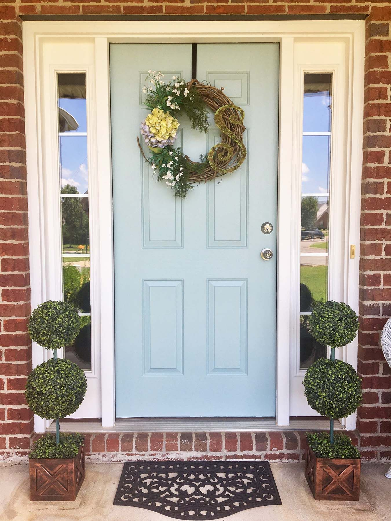 Light blue front door with wreath. Red brick house. Porch plants.