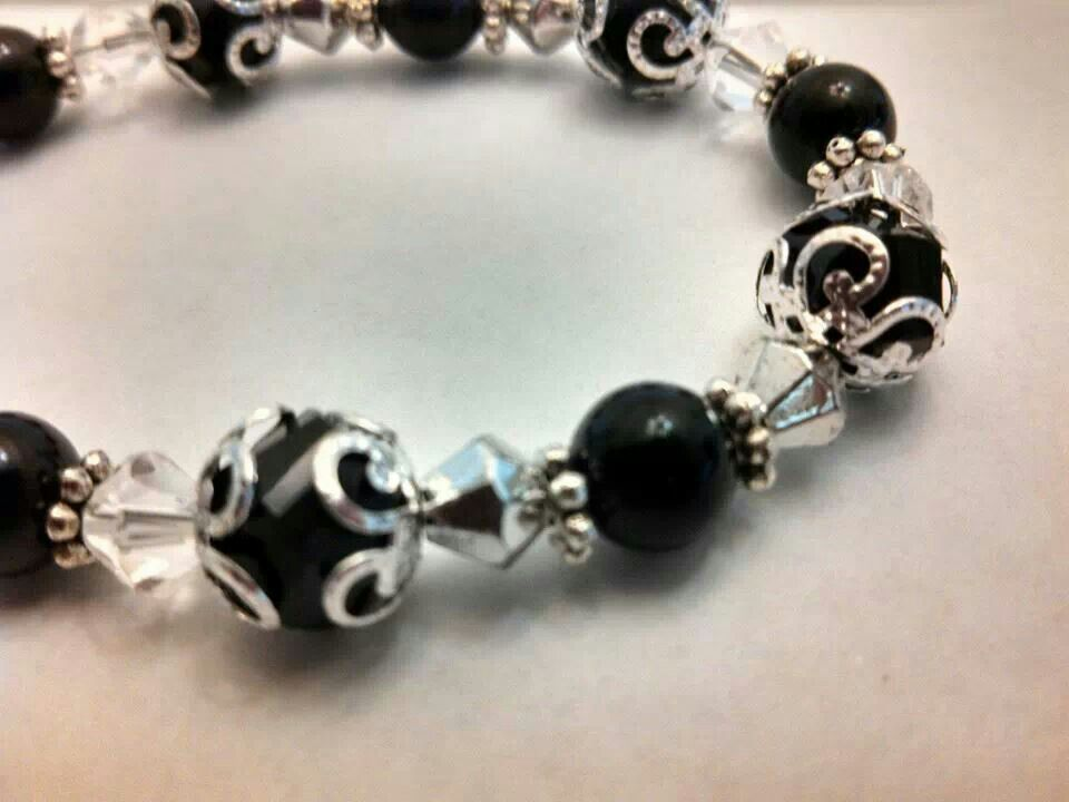 Black Glass beads, metal finding and crystals.  Handmade by me. One of a kind. Adjustable clasps.  $15.