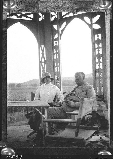 Mr. and Mrs. George Gustav Heye seated at a table in an elaborately decorated wooden summer house on top of Nacoochee Mound