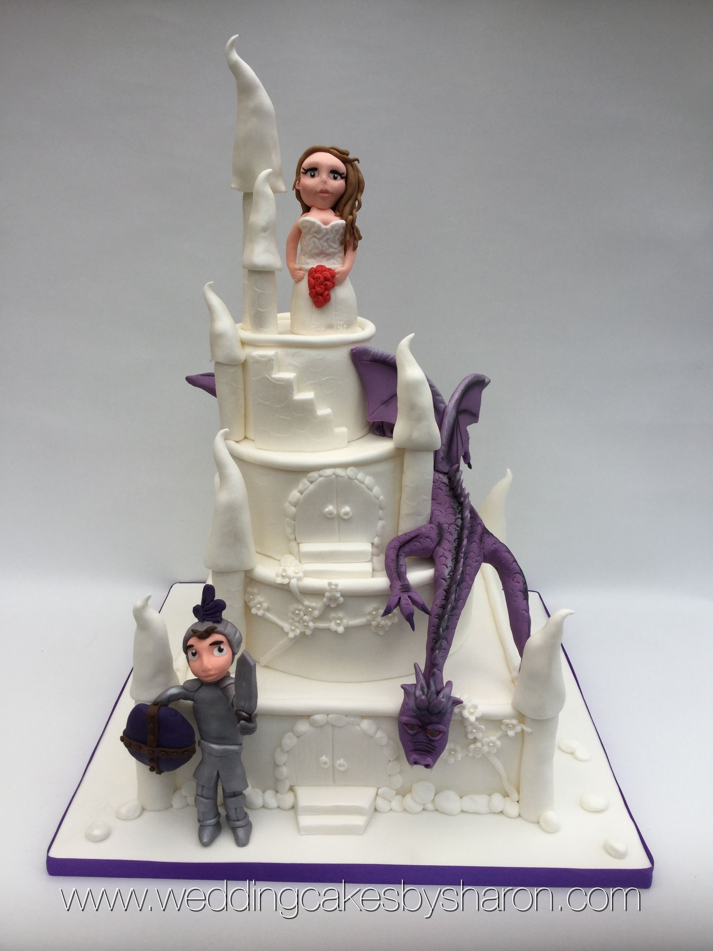white castle wedding cake with bride groom and a ferocious dragon