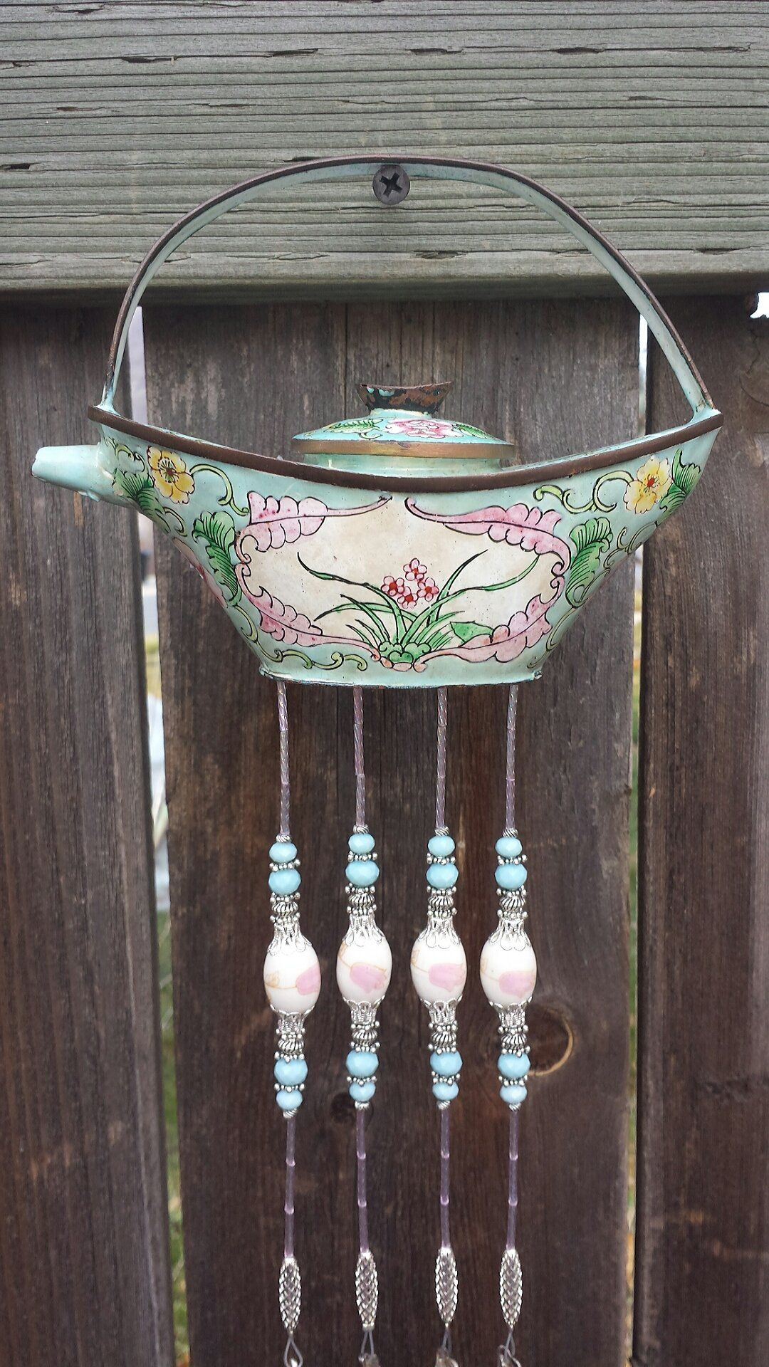"Pretty Pastel Enamel Teapot Up-cycled Into A Chime. This stunningly unique chime was made from an antique enamel teapot. This chime is ""one of a kind"" and would look great on a patio, fence, porch or the kitchen window. It is incredibly detailed with gorgeous flowers, colors, and designs. Teapot is small, measuring 6"" long and 4"" tall to top of knob on lid. Overall length of chime is approx. 20"". There are 4 antique silver plated spoons cascading from the bottom of the teapot. Antique..."