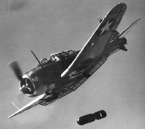 An SBD Dauntless drops its bomb. The dive brakes are extended and are visible behind the wings.