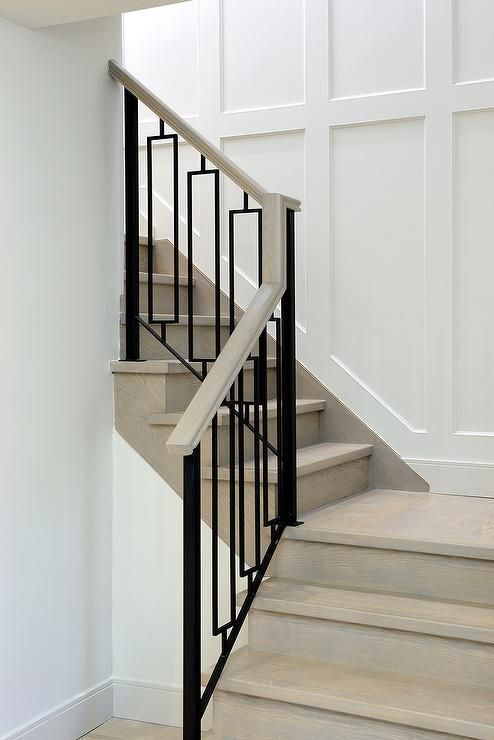 A Gray Wash Wood Staircase Is Finished With Hollow Iron Balusters Alongside A Staircase Wall Clad In Wainscoting Wood Staircase Iron Staircase Staircase Design