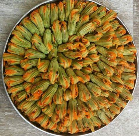 Kabak çiçeği dolması Ege'ye ve Girit'e özgü bir yemektir. Görünümü ve lezzeti muhteşemdir. Bu özel dolmayı yapmak için sabah erken toplanan kabak çiçekleri hemen doldurulup pişirilmelidir. Kabak çiçekleri sabahın erken saatlerinde güneş henüz yükselmeden toplanır. Böylece günün ilk ışıklarında çiçekler güneşi görüp yapraklarını kapatmamış olurlar. Kapanmaması için toplanmış çiçekler içiçe konur. Dolma harcının içeriğini isterseniz damak tadınıza göre değiştirebilirsiniz. Bu tarifte önemli…