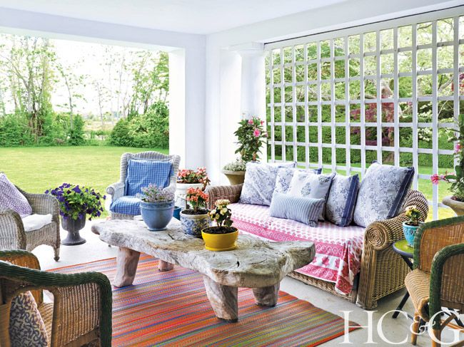 Open Patio Area With Colorful Rug Pillows And Sofa Covering Wicker