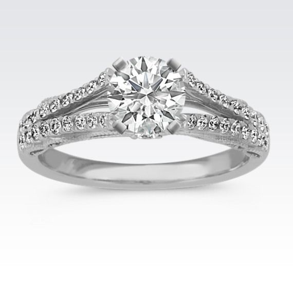Thirty-eight round diamonds at approximately .33 carat total weight create a lovely sparkle in this vintage inspired engagement ring. Crafted of premium quality platinum, intricate milgrain detailing creates a unique style on the side profile of this ring, while the split shank cathedral creates the perfect backdrop for a 1.00 carat center gemstone of your choice.
