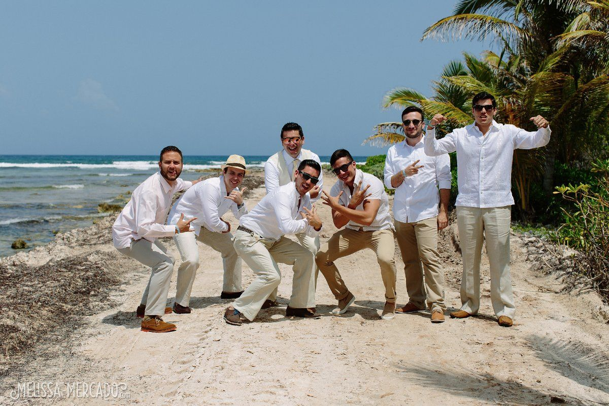 handsome groomsmen in linen white shirts and khaki pants, beach ...