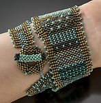 Wrap Cuff, Turquoise Patina by Julie Powell. Tiny glass seed beads woven with a needle and fishing line, bead by bead in peyote stitch. Soft and supple glass woven fabric wraps around the wrist twice and closes with a hand woven toggle closure. Shaped to be wider on one end than the other to wrap in various ways-stacked on top of each other or separated slightly.