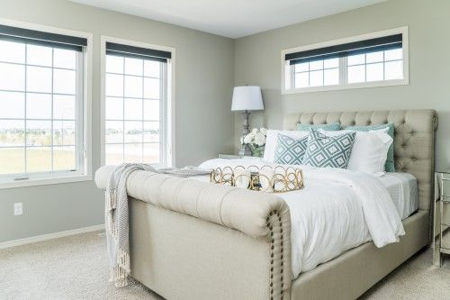 Beautiful neutral master bedroom with upholstered bed at StreetSide's Bluestem tonwhomes in Winnipeg's Sage Creek.